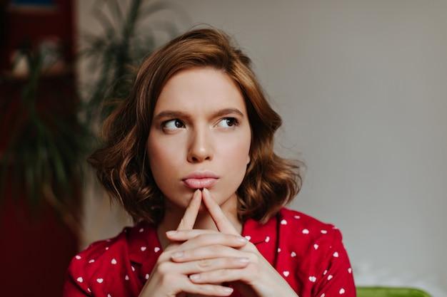 目をそらしている赤いパジャマの夢のような女性。寝間着で物思いにふける若い女性の屋内ショット。