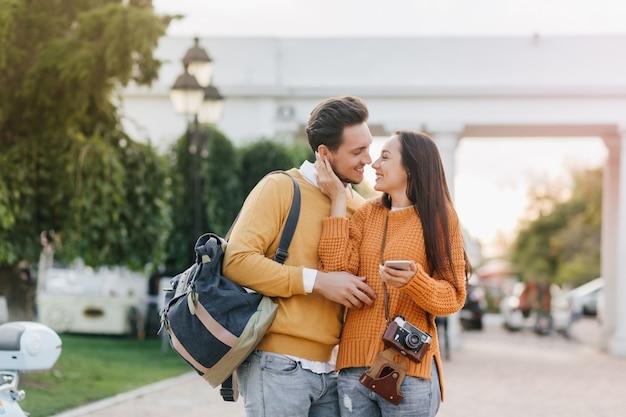 Мечтательная женщина в стильном оранжевом свитере держит смартфон и нежно трогает лицо парня