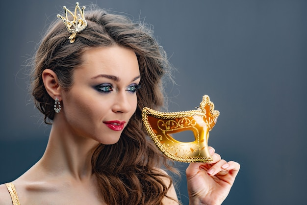 Dreamy woman looking away with a princess crown on her head and  holds a golden carnival mask in hand close-up