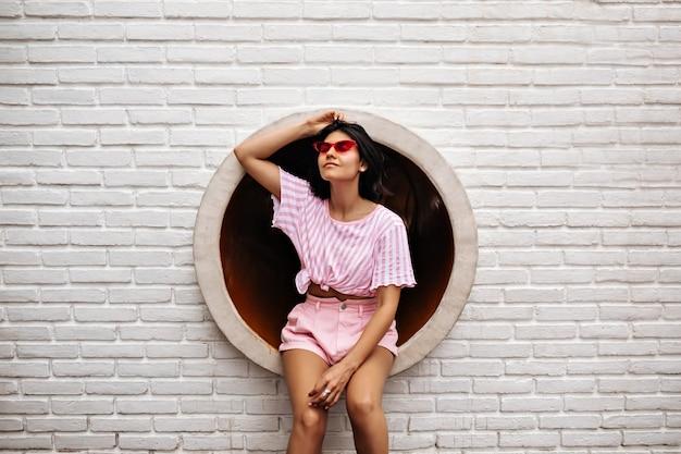흰색 벽돌로 벽에 포즈를 취하는 꿈꾸는 여자. 핑크 선글라스에 잠겨있는 무두 질된 여자의 야외 샷.