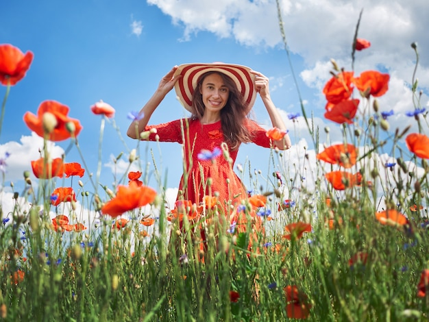 Dreamy woman in red dress and a big red striped hat in beautiful herb flowering poppy field