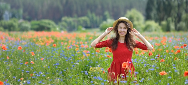 Dreamy woman in red dress and hat in beautiful herb flowering poppy field