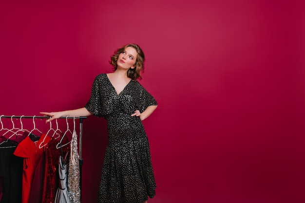 Dreamy woman in retro black dress looking up while posing beside hangers with clothes