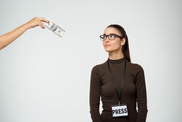 Dreamy woman smiling as looking at dollars bribe