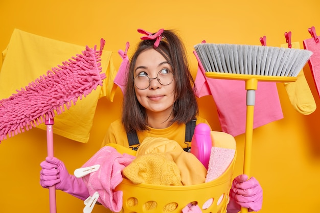Dreamy woman stands with cleaning tools concentrates thoughtfully above thinks what to do after finishing work about house poses near basin of laundry haging clothesline behind. domestic chores