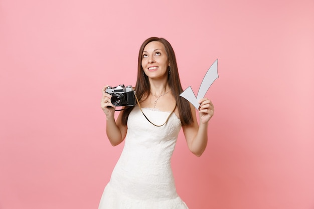 Dreamy woman in white dress looking up hold retro vintage photo camera and check mark, choosing staff photographer