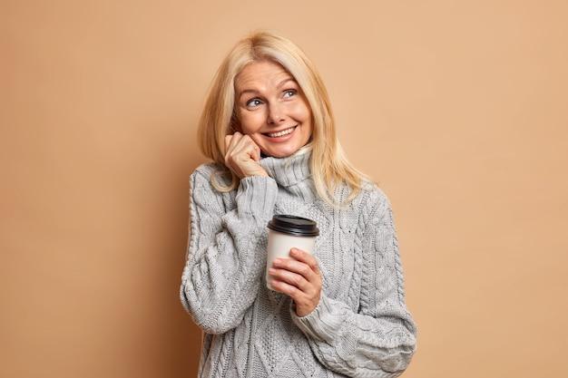暖かい灰色のセーターに身を包んだブロンドの髪の最小限の化粧をした夢のようなしわのある女性年金受給者は、何か楽しいことを夢見て、コーヒーを飲みます。