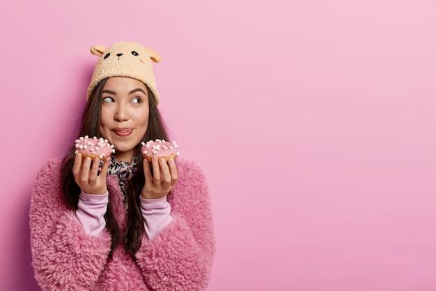 꿈꾸는 젊은 아시아 여성은 맛있는 달콤한 도넛 두 개를 들고 입술을 핥고 고 칼로리 음식을 먹고 싶어하며 다이어트를 중단하고 따뜻한 옷과 모자를 쓰고 있습니다.