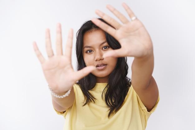 黄色のtシャツを着た夢のような若い魅力的なマレーシアの女性がカメラに向かって手のひらを引っ張ってカメラを眺めて空想と白い背景の上のロマンチックな気分で優しいポーズ