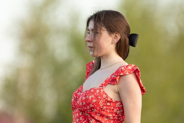 Dreamy young attractive woman in a red dress and a black ribbon in her hair