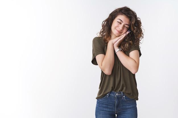 夢のような若いかわいい女性枕のような細い頭の手のひらを大きく閉じて笑って、オリーブのtシャツジーンズ、白い背景を身に着けて楽しく立って眠っているように見えます、夢が叶うと感じます