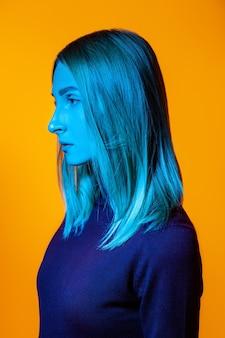 Мечтательная молодая женщина-модель в водолазке с ярким неоновым светом на лице, стоящая на оранжевом фоне с закрытыми глазами