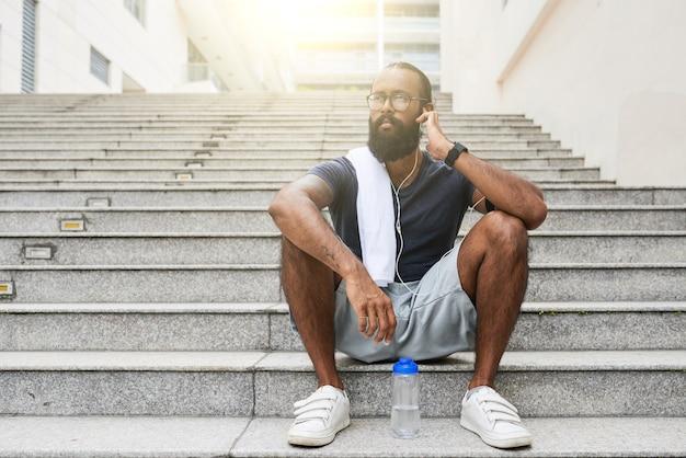音楽を聴きながら、階段に座ってイヤホンを調整する肩にタオルを持った夢のような若いインドのスポーツマン