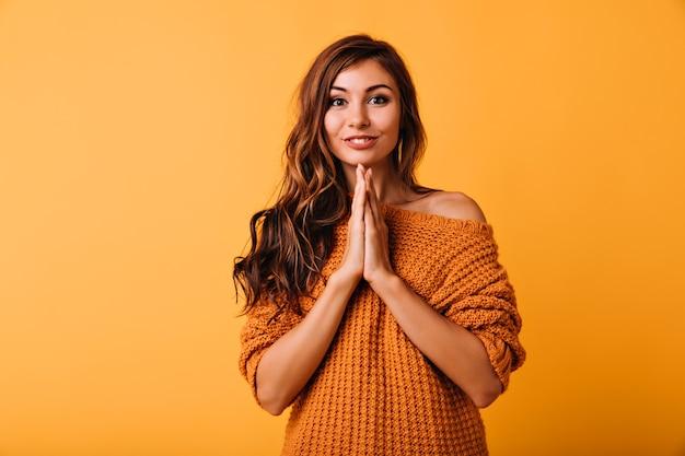 Мечтательная юная леди в стильном оранжевом свитере позирует с милой улыбкой. крытый портрет очаровательной кавказской девушки с длинными волнистыми волосами.