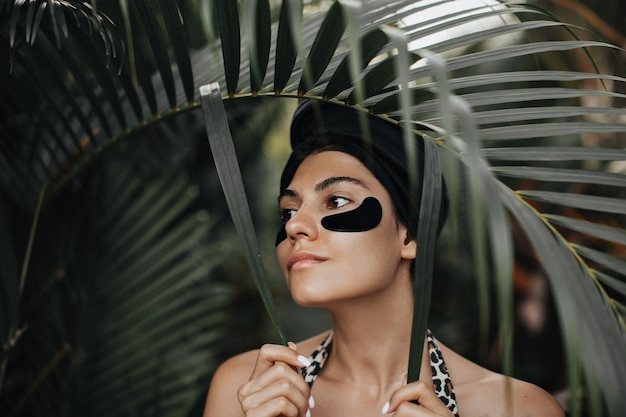Dreamy young lady with eye patches looking away. outdoor shot of romantic woman in turban posing on nature background.