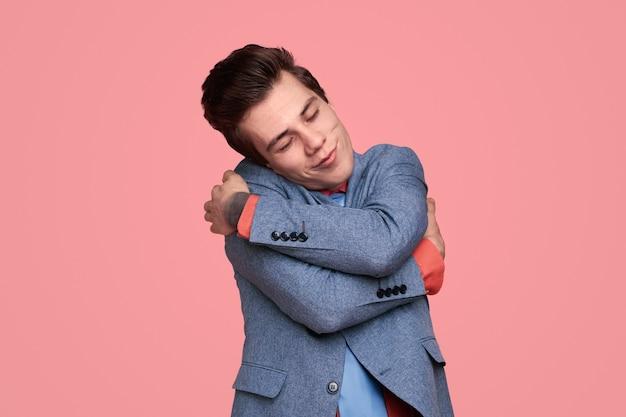 Мечтательный молодой человек, обнимающий себя