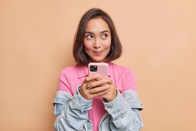Мечтательная молодая симпатичная азиатская женщина с темными волосами держит мобильный телефон с задумчивым выражением лица, думает о полученном сообщении, носит розовую футболку, джинсовую куртку, смотрит в сторону изолированно над бежевой стеной