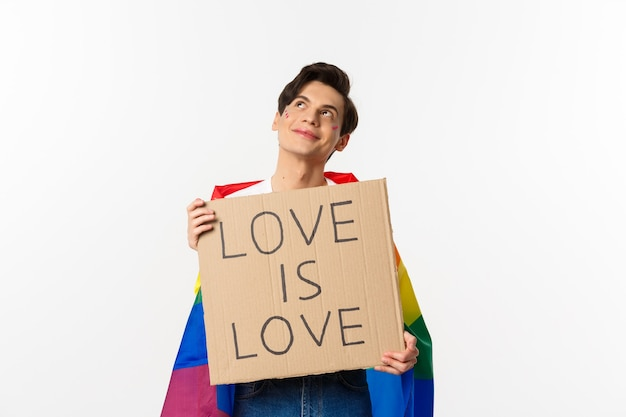 Dreamy young queer person smiling and looking at upper left corner, holding love is love sign for pride parade, wearing rainbow flag, white background.