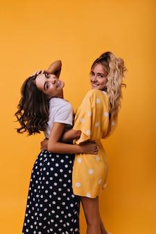 꿈꾸는 어린 자매들이 장난스럽게 뒤를 돌아보고 있습니다. 귀여운 미소로 포즈를 취하는 세련된 여자 친구의 실내 초상화.