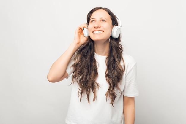 夢のような若い女性は、白い背景の上に彼女のイヤホンを使用して楽しんでいます。