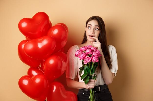 バラの花束を持ってバレンタインデーに秘密の崇拝者のことを考えている夢のような若い女性...