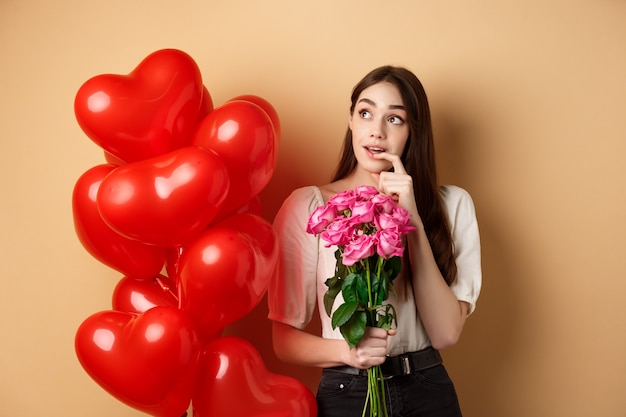 Dreamy young woman holding bouquet of roses and thinking about secret admirer on valentines day