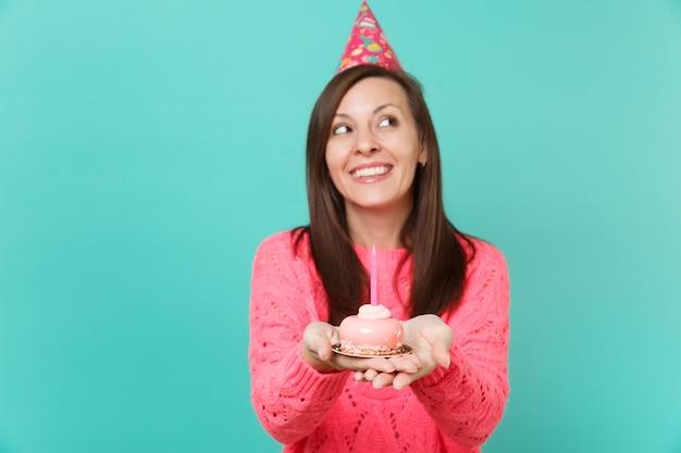 분홍색 스웨터와 생일 모자를 쓴 꿈꾸는 젊은 여성이 파란색 벽 배경 스튜디오 초상화에 격리된 촛불을 들고 손으로 케이크를 들고 있습니다. 사람들이 라이프 스타일 개념입니다. 복사 공간을 비웃습니다.