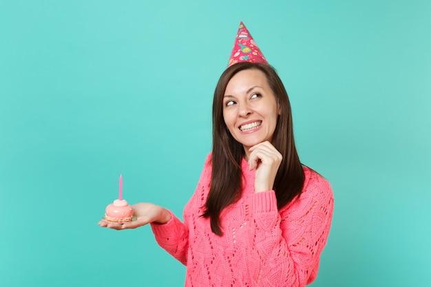 분홍색 스웨터를 입은 꿈꾸는 젊은 여성, 생일 모자를 올려다보고, 턱에 손을 올리고, 파란색 배경에 촛불을 들고 손으로 케이크를 들고 있습니다. 사람들이 라이프 스타일 개념입니다. 복사 공간을 비웃습니다.