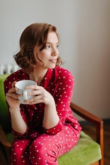 一杯のコーヒーを保持している赤いパジャマの夢のような若い女性。肘掛け椅子に座って目をそらしている物思いにふける女性の屋内ショット。