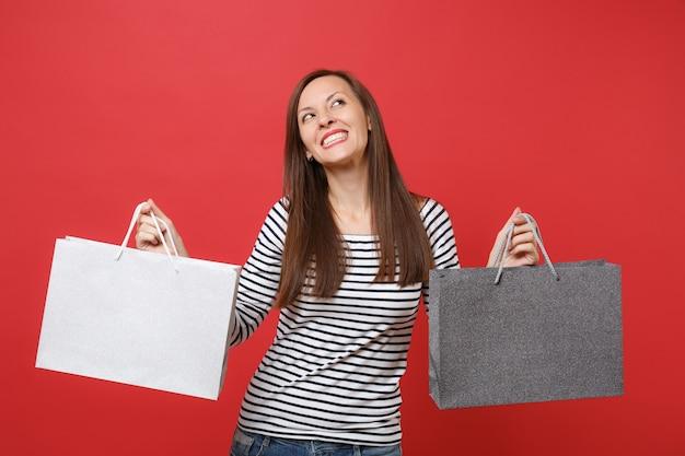 줄무늬 옷을 입은 꿈꾸는 젊은 여성이 붉은 벽 배경에서 격리된 쇼핑 후 구매한 패키지 가방을 들고 위를 올려다보고 있습니다. 사람들은 진심 어린 감정, 라이프 스타일 개념입니다. 복사 공간을 비웃습니다.