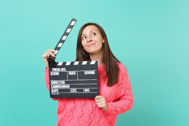 Dreamy young woman in knitted pink sweater looking up, holding classic black film making clapperboard isolated on blue wall background, studio portrait. people lifestyle concept. mock up copy space.