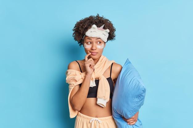 夢のような若い女性は脇に目をそらし、目の下にコラーゲンパッチを適用してしわを減らし、青い壁に隔離されたパジャマを着た枕を細い線で保持します