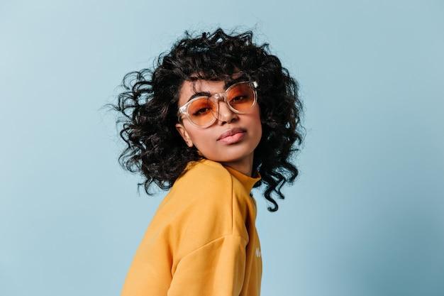 Giovane donna vaga in occhiali da sole che esaminano davanti