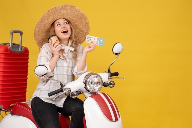 꿈꾸는 젊은 여자 모자를 쓰고 오토바이에 앉아 노란색에 커피와 티켓을 들고