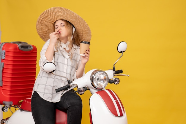 Dreamy young woman wearing hat and sitting on motorcycle and showing ticket