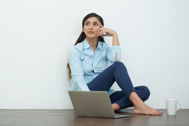 Мечтательный молодая женщина с ноутбуком и чай на полу