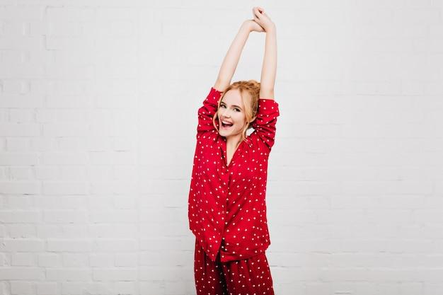 朝に伸びる表情が嬉しい夢のような若い女性。赤いナイトスーツで写真撮影を楽しんでいるかわいいヨーロッパの女の子。