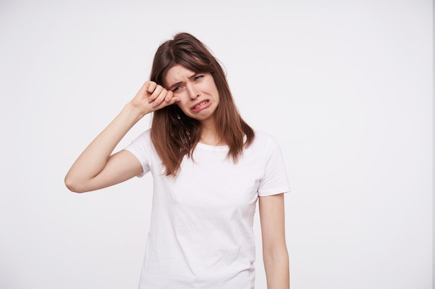 Dreary young brunette lady with casual hairstyle wiping tears and frowning sadly her face while standing over white wall in white basic t-shirt