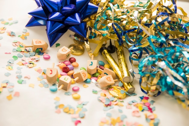 Dreidels and candies near confetti and tinsel