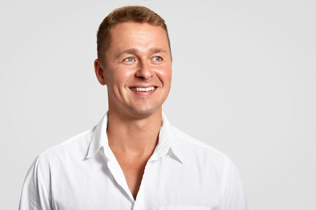Dremy blue eyed male with positive expression, broad smile, shows white teeth, looks into distance, thinks about something, wears elegant shirt, isolated over white wall with blank space