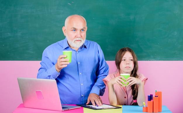 Пропитанный гордостью. маленькая девочка с учителем человека учиться на компьтер-книжке. школьный урок онлайн. написание эссе. новые технологии в обучении. онлайн-образование. обратно в школу. зрелый учитель помогает школьнице.