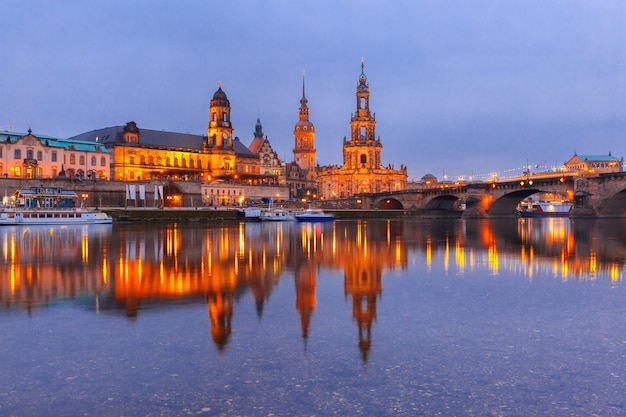 Dresden cathedral of the holy trinity, bruehl's terrace and augustus bridge with reflections in the river elbe at night in dresden, saxony, germany