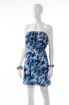 Платье и браслеты на манекен. женский манекен в платье без бретелек. синее платье с цветочным принтом и браслеты. классические наручные часы и одежда.