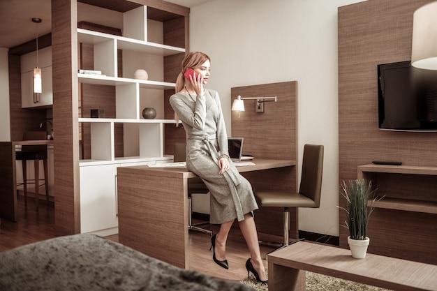 ドレスと靴。長いドレスとかかとの高い靴を身に着けているスリムでスタイリッシュなブロンドの髪の実業家
