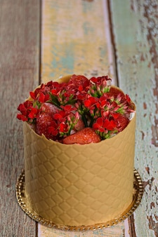 Dress cake, wrapped in a textured layer of salted caramel chocolate, with strawberries and red kalanchoe flowers (vertical photo).