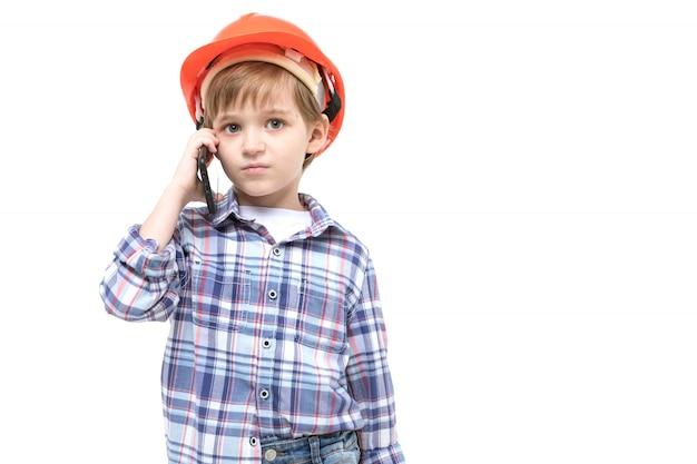 オレンジ色のヘルメットとシャツでフォアマンにdressした愛らしい子供