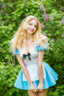 不思議の国のアリスにdressした長い髪の美しい若いブロンドの女性の肖像画。ライラックの茂みの近くの自然の女性。