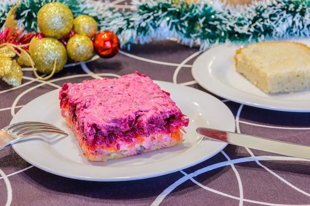 Одет селедку или селедку под шубу. символ нового года. традиционная русская кухня. рождественские украшения в фоновом режиме. новогодняя концепция.