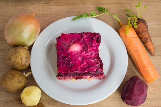 Одет селедку или селедку под шубу. традиционная русская кухня. слоеный салат из нарезанной кубиками маринованной сельди, покрытый слоями вареных тертых овощей и майонеза.