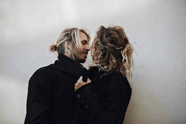 Одетые в черные джинсовые куртки мальчик и девочка с красивыми глазами начинают целоваться